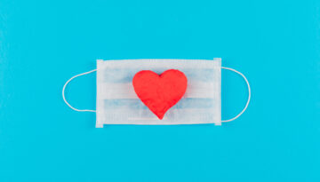 Top view heart on a medical mask on cyan blue background. horizontal